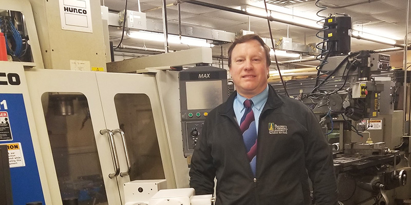 Michael W. Lane in front of equipment