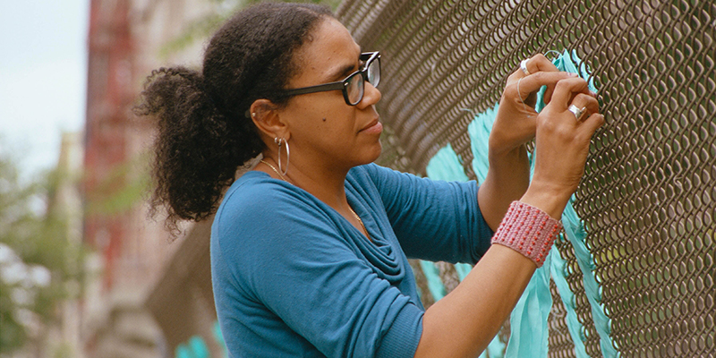 Mildred Beltre weaving material into a Brooklyn roadside metal fence.