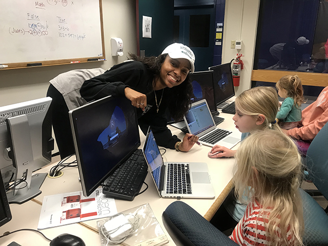 Student Nikki Allen in computer lab teaching coding skills to young girls