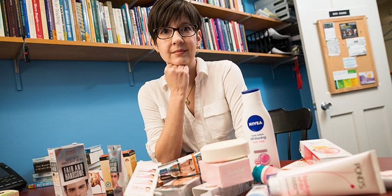 Professor Nikki Khana sitting at her office desk with a pile of whitening creams in front of her.