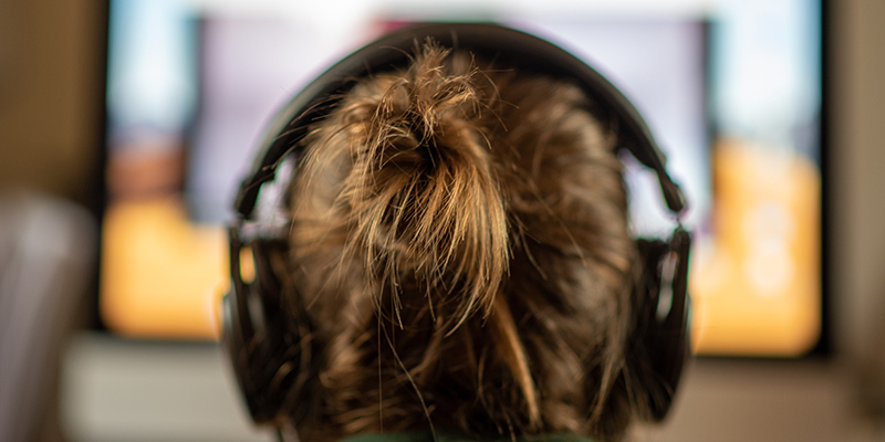 girl wearing headphones staring at computer screen, seen from behind