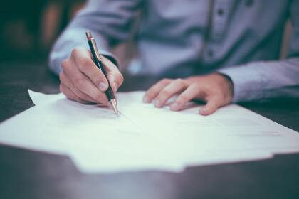 Photo of man signing papers