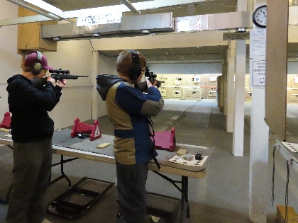 2 students hold rifles as they compete in an indoor shooting competition