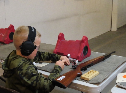 1 student loads his rifle as he competes in an indoor rifle competition