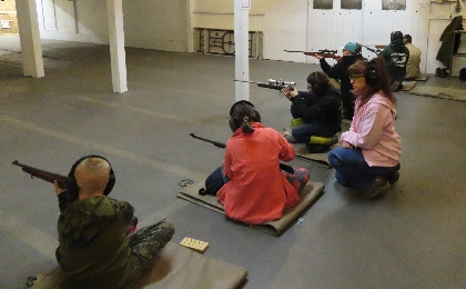 4 students hold rifles as they compete in an indoor shooting competition