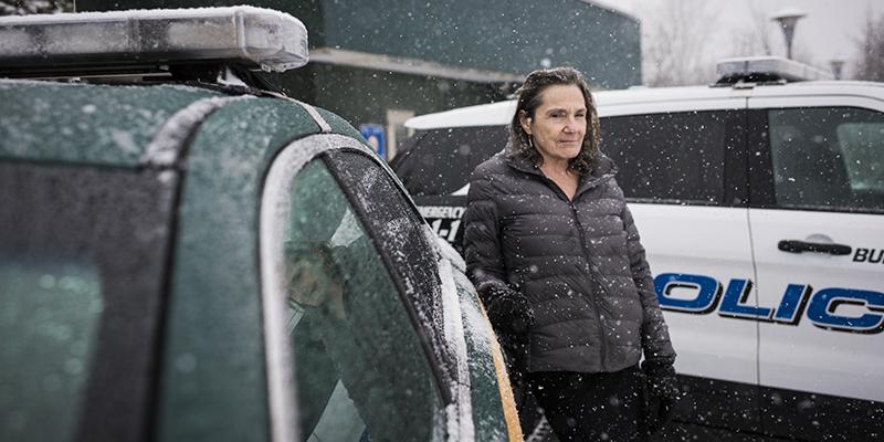 Stephanie Seguino outside a police car in snow