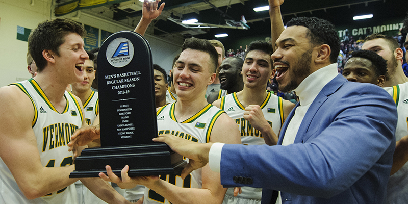 Skyler Nash with men's basketball teammates cheers with America East trophy