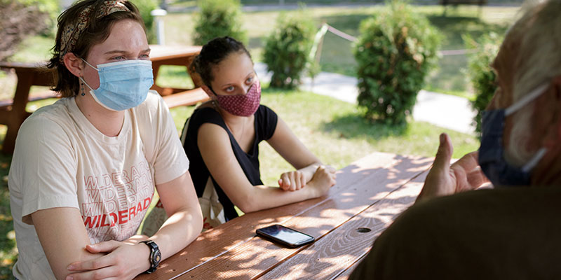 Two students interview a man at a picnic table.