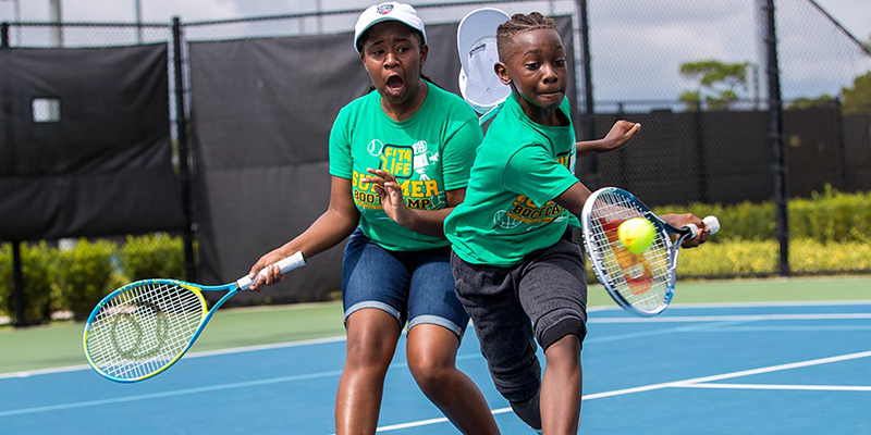 Two children play tennis