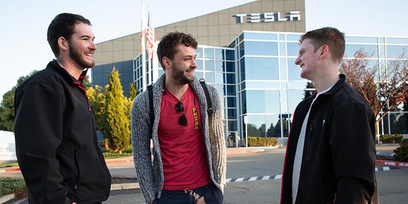 3 students in front of Tesla showroom