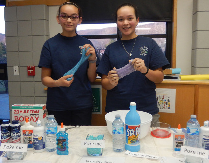 Students at tabletop display about tropical slime