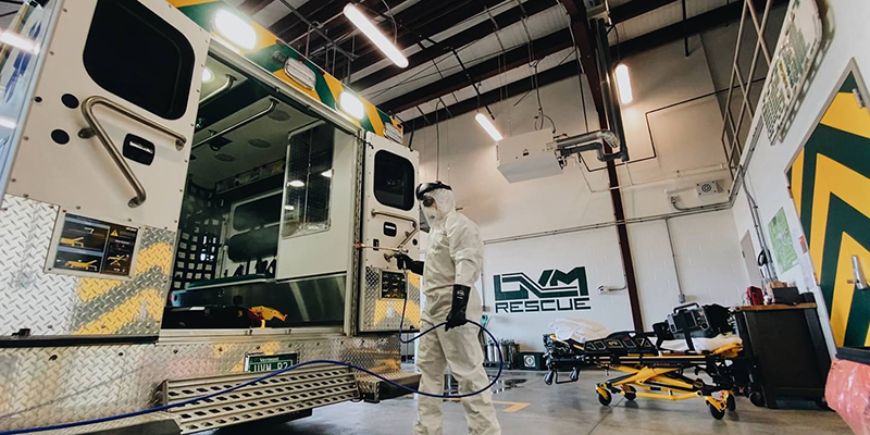 Student staffer cleans ambulance interior while dressed in protective gear.