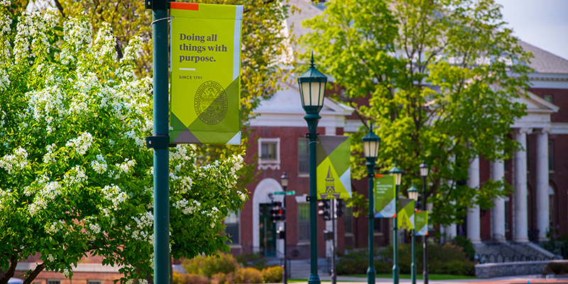 "Waterman Building framed by a banner on the Green that reads ""Doing all things with purpose"""