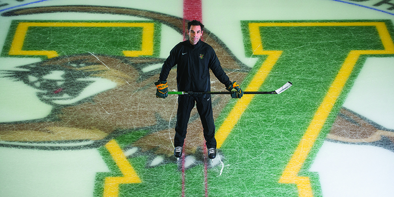 Coach Todd Woodcroft on the ice over the catamount logo