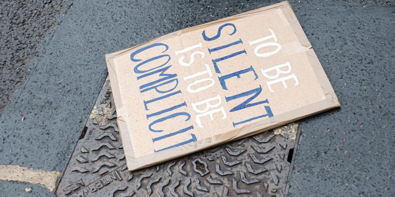 """protest sign on street reads """"To be silent is to be complicit"""""""