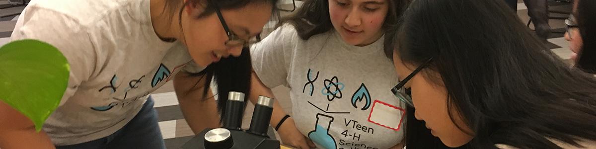 Three teens look at microscope