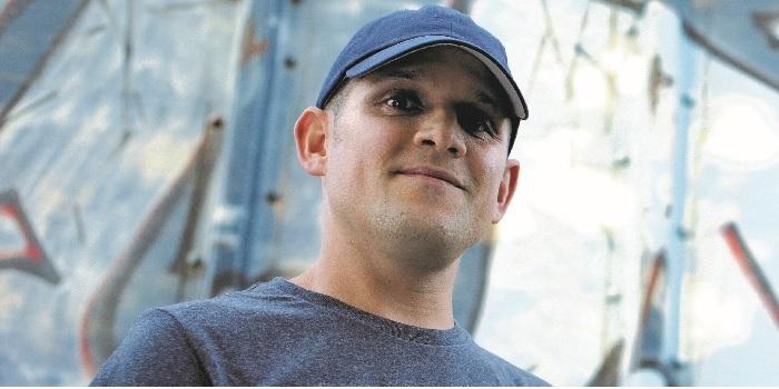 Stephen Cramer wearing baseball cap, looking down into camera