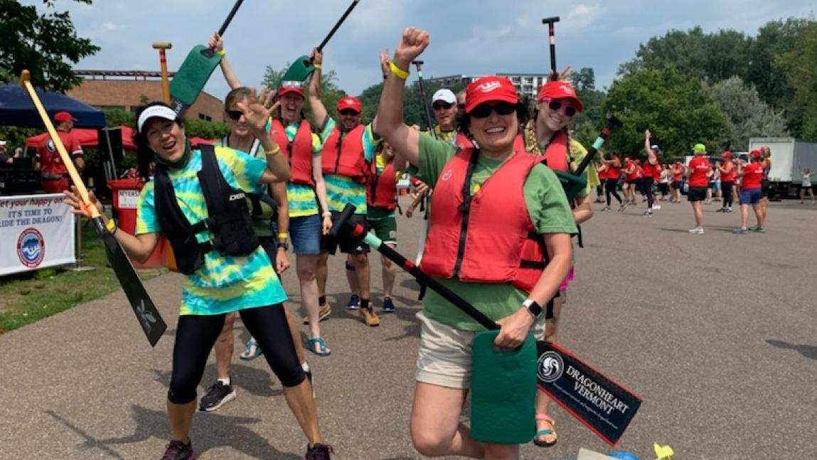 Several people outdoors wearing colorful clothes and life jackets, holding paddles, arms raised, smiling