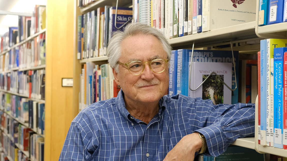 Allan Kellehear leaning on a shelf of books in a library like setting