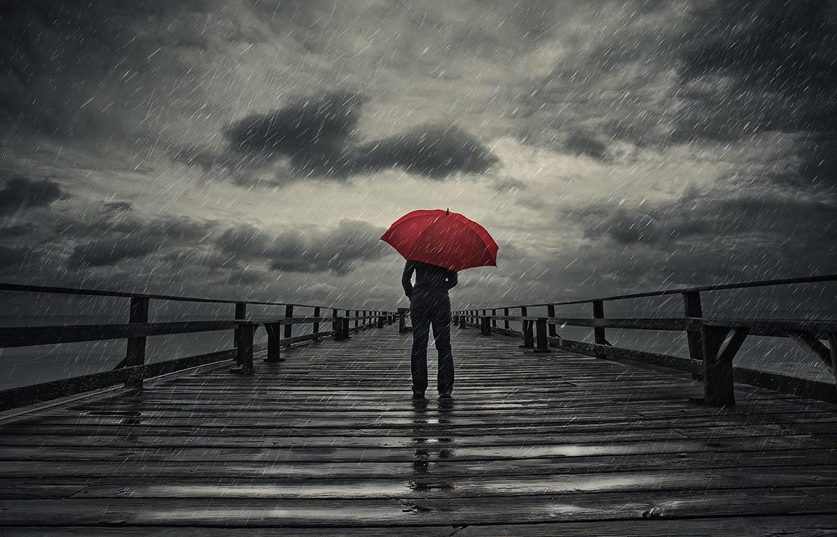 person holding umbrella in storm