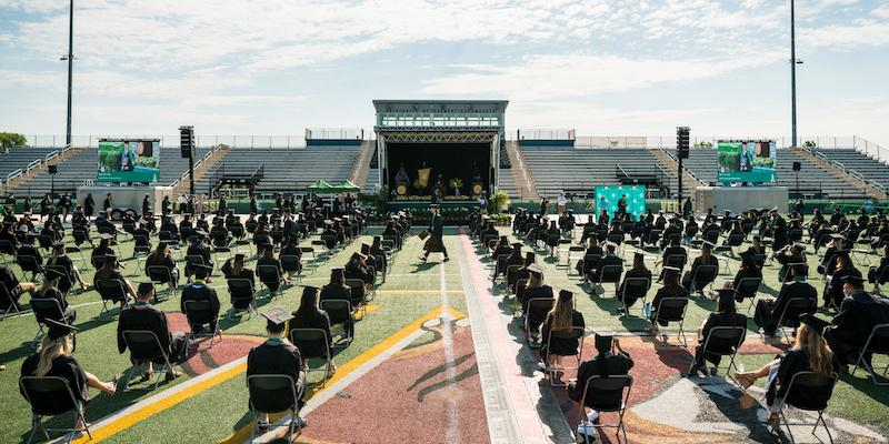 graduates seated in chairs 6 feet apart on the University of Vermont field with commencement stage in the background