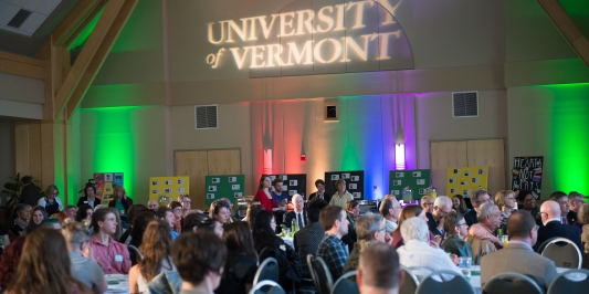 Audience gathered in Davis Center for Rainbow Graduation and Awards ceremony. UVM logo projected on wall with rainbow lighting.