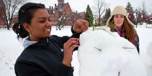 A student builds a snowman on the campus green