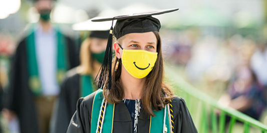 female student wearing regalia and a yellow mask with a smile on it