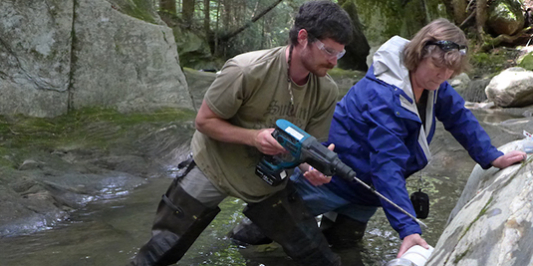 Grduate students installing a suspended sediment sampling device in a river channel