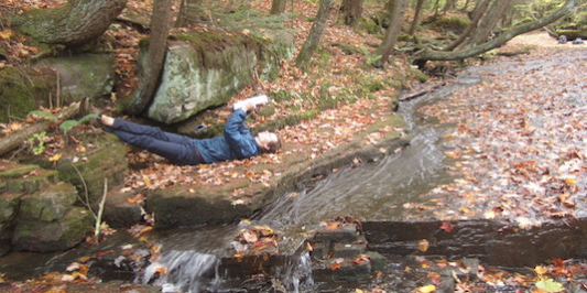 a man lies next to a stream in autumn, holding a notebook over his head
