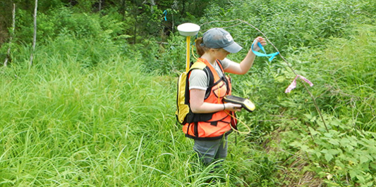 Student intern using GPS equipment in a field