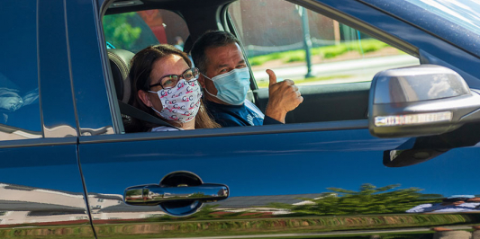 Two people in a car wearing safety masks