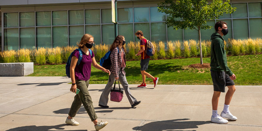 Students walking on the campus of UVM safely distancing with face masks