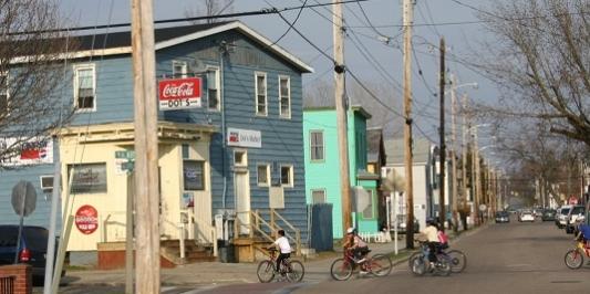 Children ride bikes down a city street.