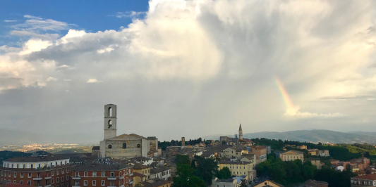 Italian town skyline with bell tower and rainbow