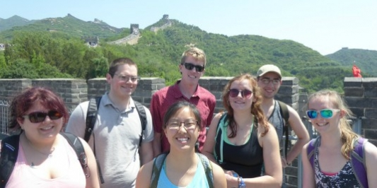 """Smiling students pose in front of the """"great wall"""""""