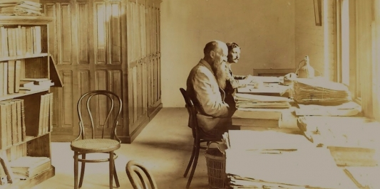 sepia photo of two men seated at their mounting table