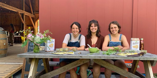 Three students sitting at picnic table in front of a barn