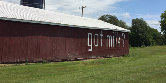 image description: low red barn with the words 'got milk?' painted in white on the side, under a clouded blue sky with green grass and trees in the background