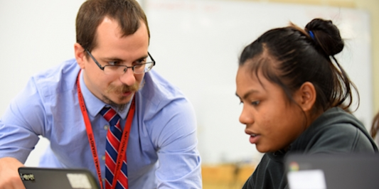 UVM alumnus Thomas Payeur works with a student at Winooski High School.