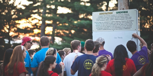 Students signing common ground boards at twilight induction