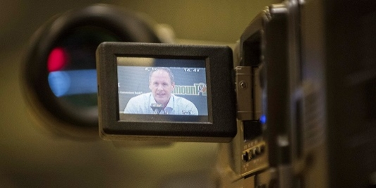 A shot of the screen on a video camera capturing an interview with a UVM official.
