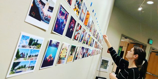 students installing rows of square photos on a wall
