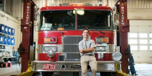 Student employee poses in front of a fire engine