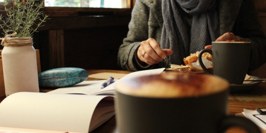 view of person's hands writing at a table with coffee and books