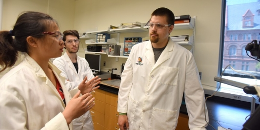 Graduate students engage in a laboratory setting.