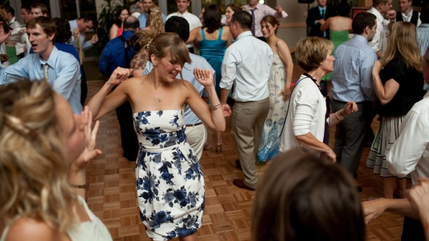 blonde woman in a dress dancing in a room full of people at a wedding reception