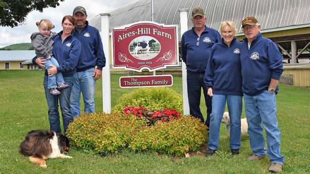 Employees of Aires Farm standing near sign
