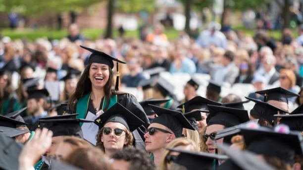 girl smiling above crowd at UVM graduation
