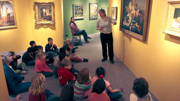 A group of elementary students view paintings in the European/American gallery